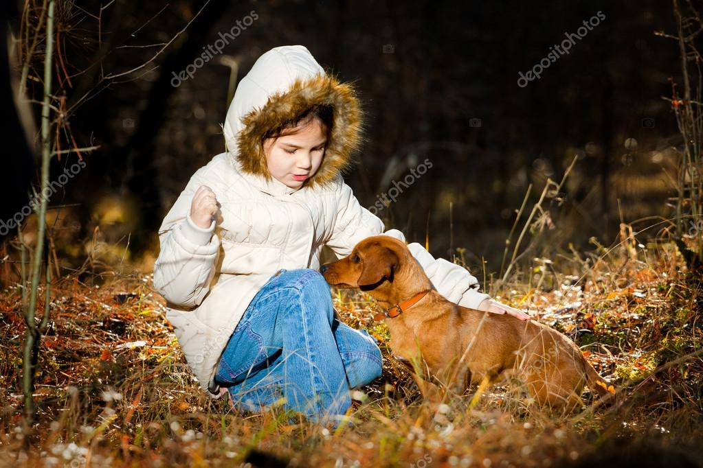 Happy little girl playing with big dog in the forest in autumn