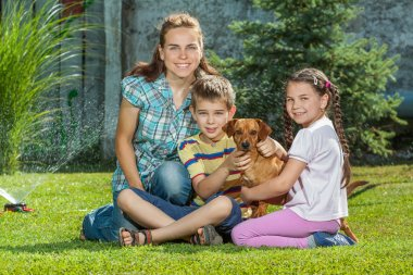 A beautiful mother, son and daughter family with their pet dog,