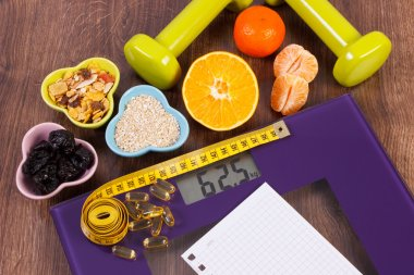 Digital scale with tape measure, tablets, dumbbells, fruits, muesli, slimming concept