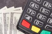 Platební terminál, čtečka kreditních karet a peníze. Koncept bezhotovostní nebo hotovostní platby za nákupy