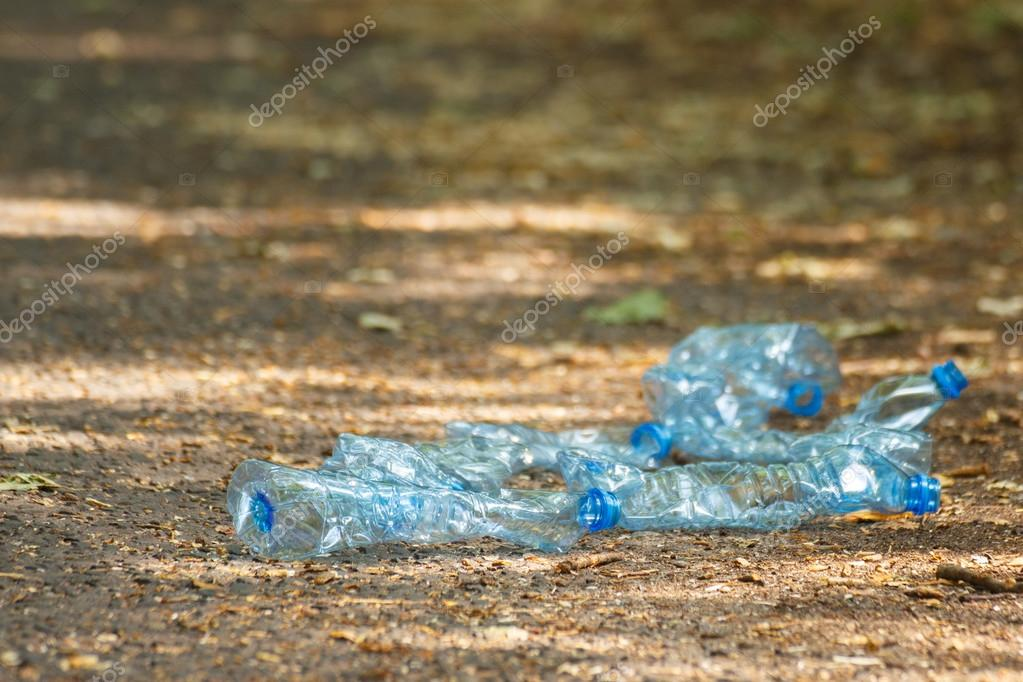 Plastic bottles of mineral water on path in park, littering of environment