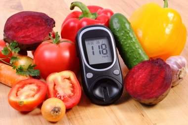 Vegetables and glucometer on wooden surface, healthy lifestyle, nutrition, diabetes