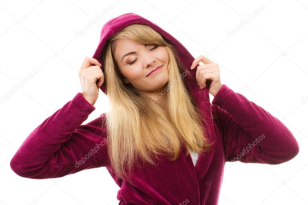 Glückliche lächelnde Frau in lila Bademantel mit Kapuze, genießen ...