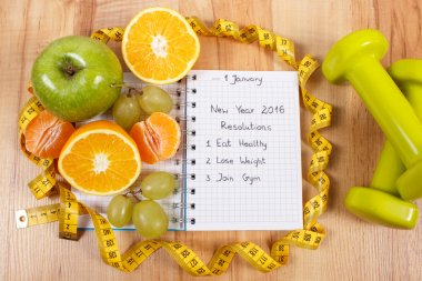 New years resolutions written in notebook and fruits, dumbbells with centimeter