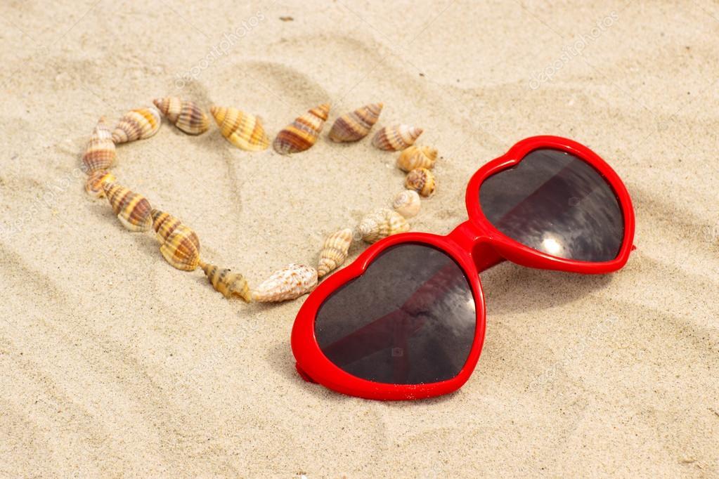 Herzen von Muscheln und Sonnenbrille auf Sand am Strand — Stockfoto ...