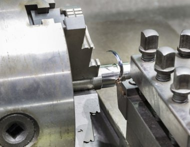Operator grooving steel bar by turning lathe