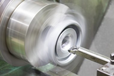 operator turning automotive parts by cnc lathe