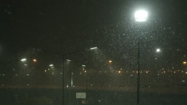 snow comes in the light of the lantern illuminating the night urban city in the parking lot