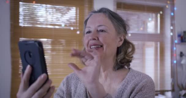 Ein älteres Ehepaar im Ruhestand kommuniziert per Videoanruf mit seinen Verwandten. Lustiger Opa mit Trompete kommt ins Gespräch.