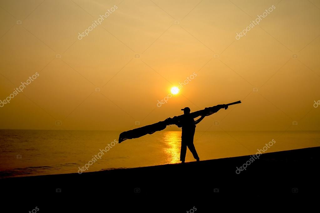 Silhouettes of a man walking carrying a timber beside the sea.