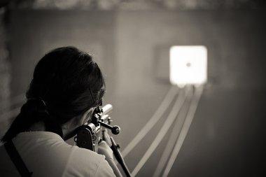 Rear view of girl  shooting target with gun