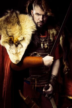 Portrait of angry viking warrior with leather, fur and sword, bo