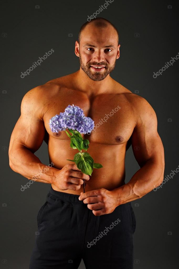 Portrait of muscular man with flower