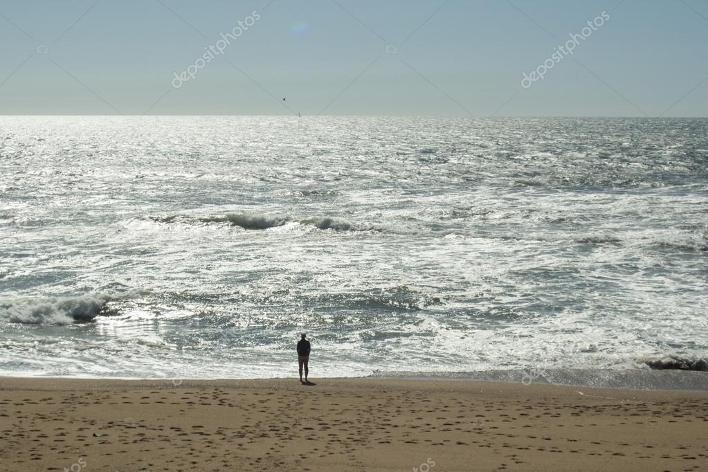man standing at beach and looking at ocean