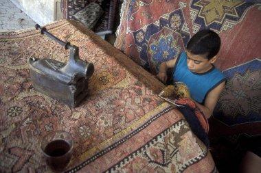 boy weaving carpet at workshop