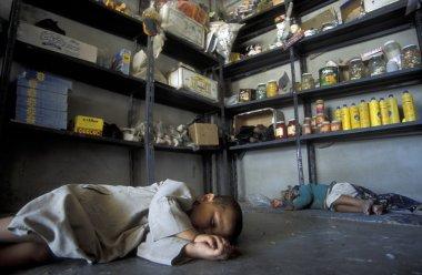 children sleeping on floor of convenience store