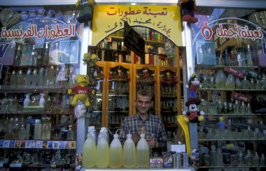 vendor standing at counter with perfumes