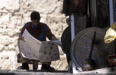 young vendor reading newspaper