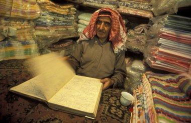 Arab vendor at counter with traditional carpets