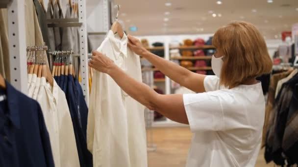 Život po odchodu do důchodu. Středního věku dáma v masce obličeje vybírá bílou košili v obchodě s oblečením