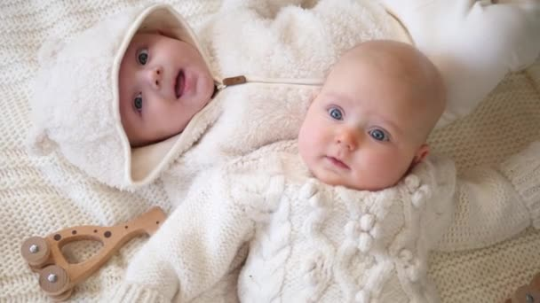 Twin Babies Wearing Stylish Fashionable Clothes Lying Together.