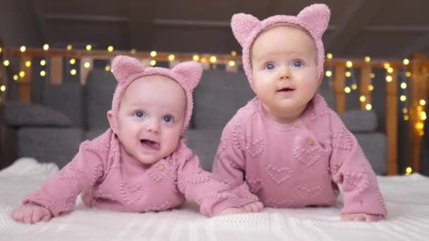 Happy Twin Babies Lying Together At Home In Pink Sweaters And Kitty Ears.
