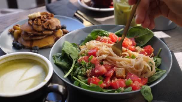 Warmer Nudelsalat mit Blättern und Gemüse. Gesunder leckerer veganer Brunch im Freien. Stapel von Pfannkuchen und Getränken im Hintergrund.