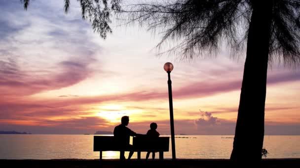 Padre e figlia si siedono sulla spiaggia contro il tramonto