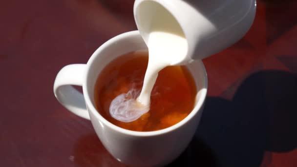 Nalil mléko z krabice od mléka porcelán do šálku s čajem. Zpomalený pohyb