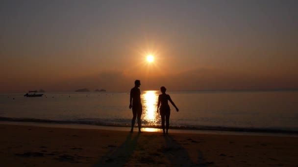 Happy Cheerful Couple Enjoying Sunset at Beach with Arms Raised up