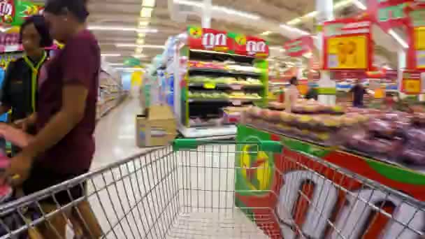THAILAND, KOH SAMUI, 05.25.2015: Men with Shopping cart moving through supermarket aisles and put food in the basket