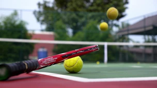 tenisová raketa s míčky na antukový tenisový kurt