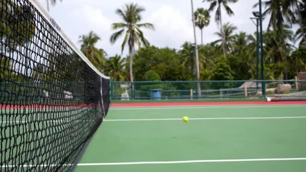 Tenisový míček zasáhne čisté pozadí. Zpomalený pohyb.
