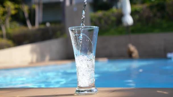 Gießen frisches Wasser in ein Glas in der Nähe von Schwimmbad. Zeitlupe.