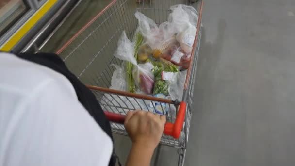 Thajsko, prosinec, 2014 - záběr ženy s nákupní košík v supermarketu.