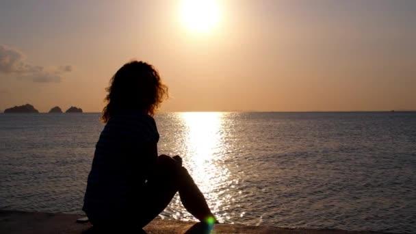 Silueta ženy relaxaci na pláži při západu slunce nad mořem.