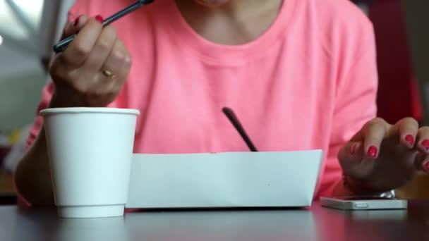 Žena jí v Cafe a pomocí mobilního telefonu