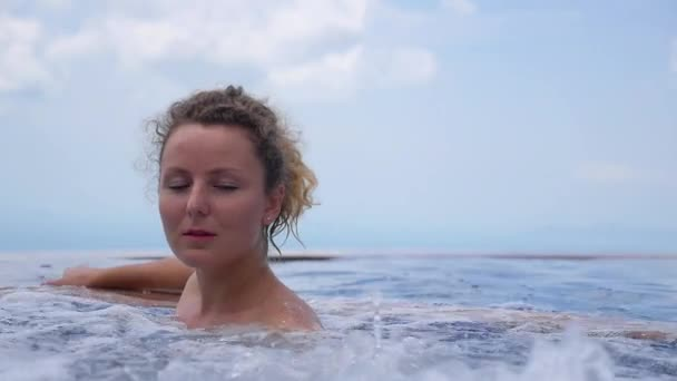 Fiatal nő a pihentető medencében. Lassú mozgás