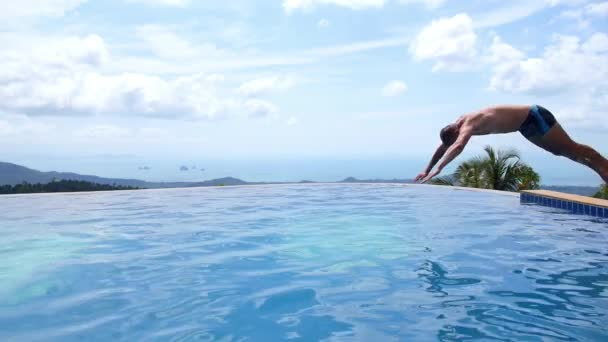 Mann, springen und Tauchen in die unendlichen Pool im Freien. Zeitlupe