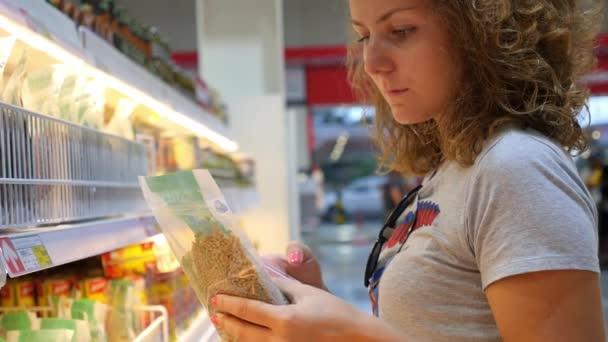 Mladá žena v supermarketu pomocí Smartphone