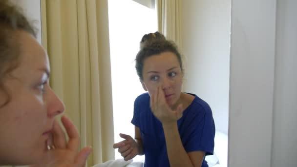 Mladá žena aplikovat make-up korektor nadace kolem očí