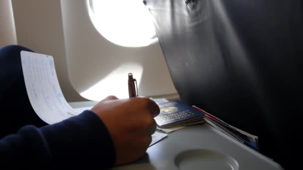 Passenger in Airplane with Passport Fill In Arrival Card