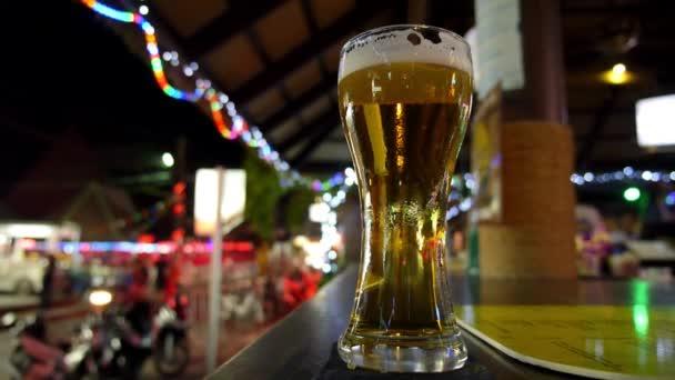 Glas schäumendes frisch gezapftes Bier auf der Theke in der Nachtstraße