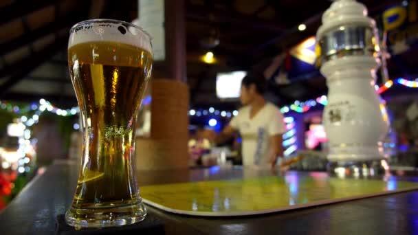 Světlé výčepní pivo v hospodě na baru s barmanem.