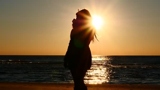 Womans silhouette drink hot tea at a seashore slow motion