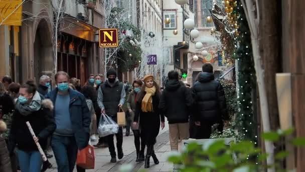 Eine belebte Einkaufsstraße in Straßburg. Die Zeit der Epidemie. Alle Menschen tragen Masken. Ein schönes Mädchen geht in einer engen Menschenmenge.