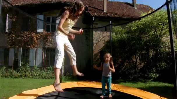 Dvě sestry, skákání na trampolíně v zahradě