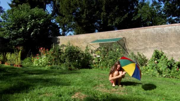 Zwei glückliche Schwestern spielen mit Gartenbewässerung im Hinterhof