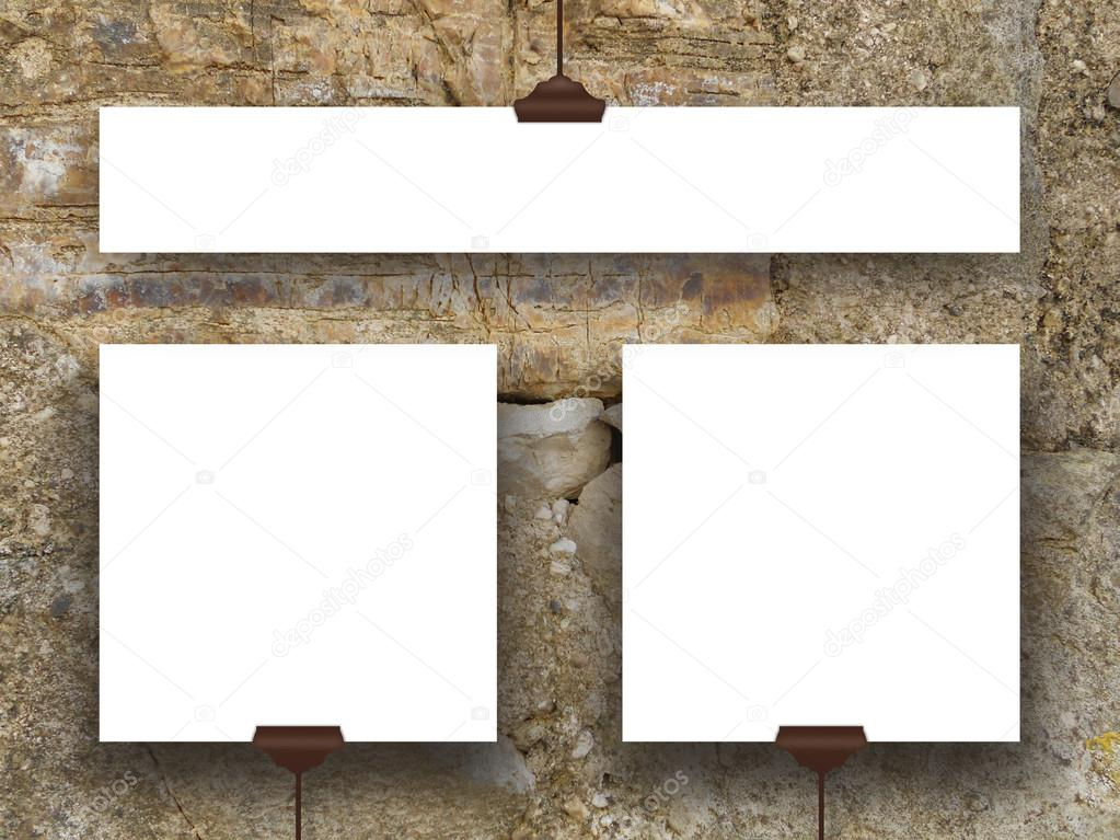 Three hanged square and rectangular frames on weathered stone wall ...