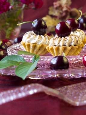 Cakes (cupcakes) with dark cherries on glass plate